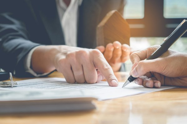 image of hand signing documents - Jon C. Correll is a workers compensation attorney